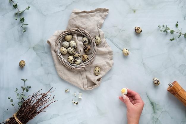 Wachtel ostereier und natürliche frühlingsdekorationen und eukalyptus. flach auf marmortisch liegen.