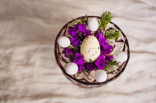 Wachtelei liegt auf violetten blüten in einer schüssel