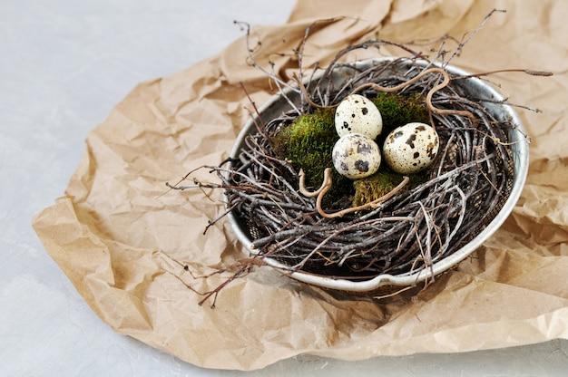 Wachteleier auf grünem natürlichem moos in einem nest von niederlassungen hergestellt in einem alten eisensieb. umweltfreundliche retro-konzept-postkarte für ostern.