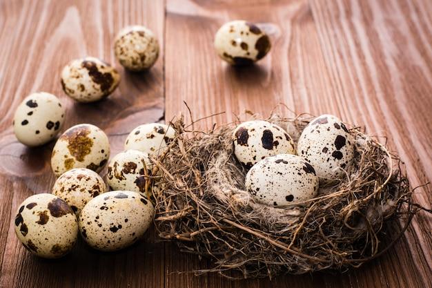 Wachteleier im nest und auf einem holztisch