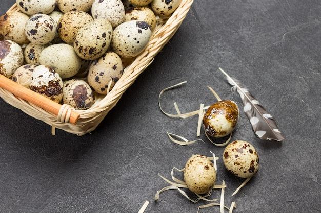 Wachteleier im weidenkorb. ei und feder auf dem tisch. flach liegen. speicherplatz kopieren