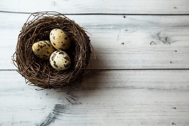 Wachteleier in einem nest auf hölzernem hintergrund