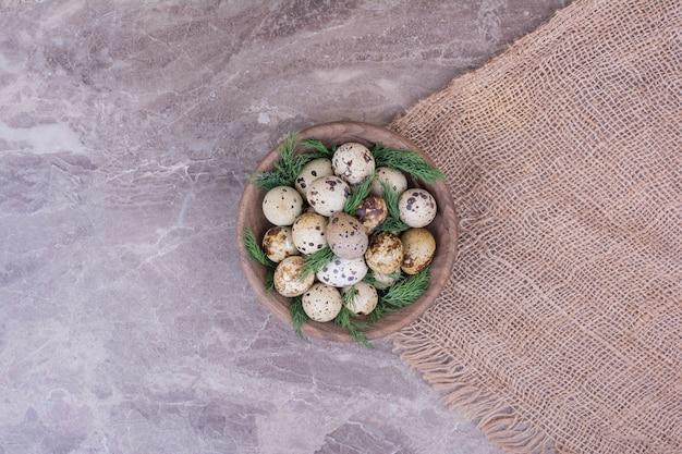 Wachteleier in einer holzschale mit kräutern