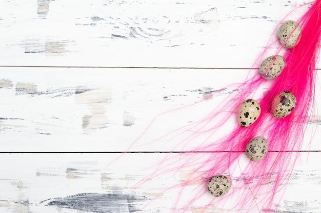 Wachteleier mit rosa federn auf weißem hintergrund. osterkonzept. freier kopierplatz.