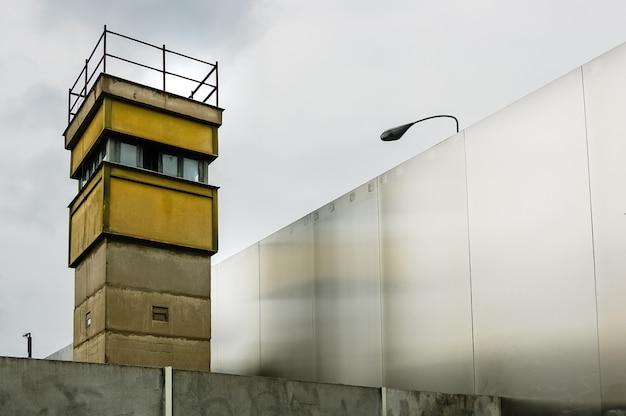 Wachturm neben einer mauer an einer grenze, um illegale einwanderer zu kontrollieren.