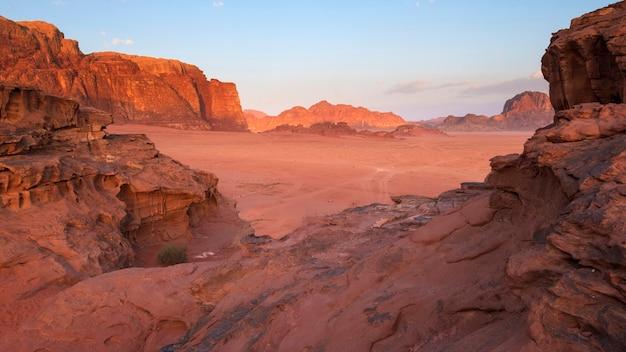 Wadi rum wüstenlandschaft in jordanien mit bergen und dünen bei sonnenaufgang