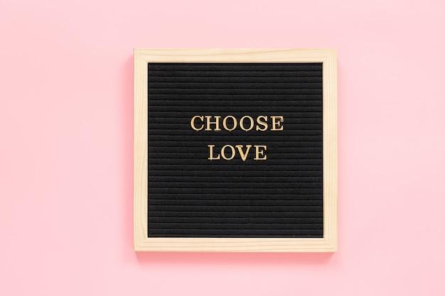 Wählen sie die liebe. motivzitat in den goldbuchstaben auf brett der schwarzen schrift auf rosa hintergrund
