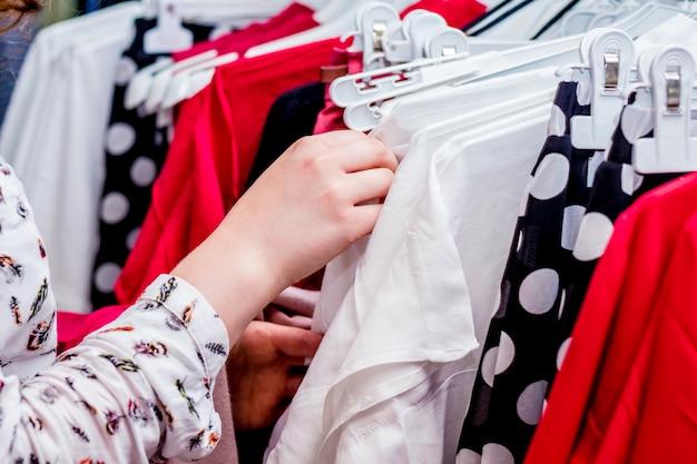 Wählen sie kleidung in einer trendigen boutique. verkauf von modischer kleidung