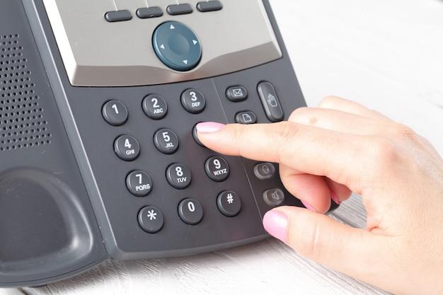 Wählen von voip-telefon im büro, tastatur und monitor detail