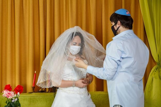 Während der chupa-zeremonie in der synagoge bedecken das maskierte brautpaar die braut mit einem schleier in der tradition des badeken