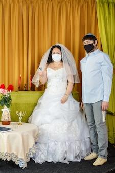 Während der chuppa-zeremonie bei einer jüdischen hochzeit in der synagoge steht das brautpaar neben dem bräutigam und hält ein glas wein in der hand des brautpaares in einer schutzmaske