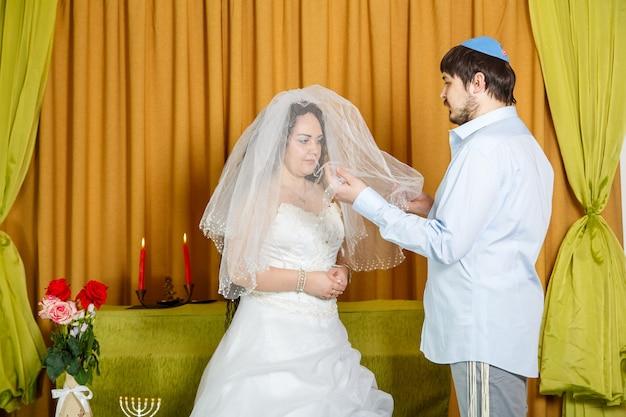 Während der chuppa-zeremonie in der synagoge bedeckt der bräutigam die braut bei der badeken-zeremonie mit einem schleier. horizontales foto
