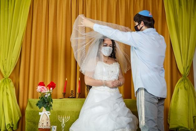Während der chuppa-zeremonie in der synagoge hebt das maskierte brautpaar den schleier vom gesicht der braut. horizontales foto