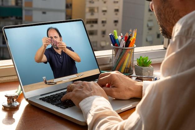 Während der coronavirus-pandemie in seinem büro vor dem fenster spricht der arzt per telemedizin mit seinem patienten. er zeigt die medikamente, die verwendet werden