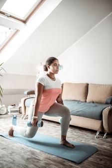 Während der yoga-sitzung. stark involvierte dame, die blaue hanteln trägt und mit ihnen auf gummimatte hockt