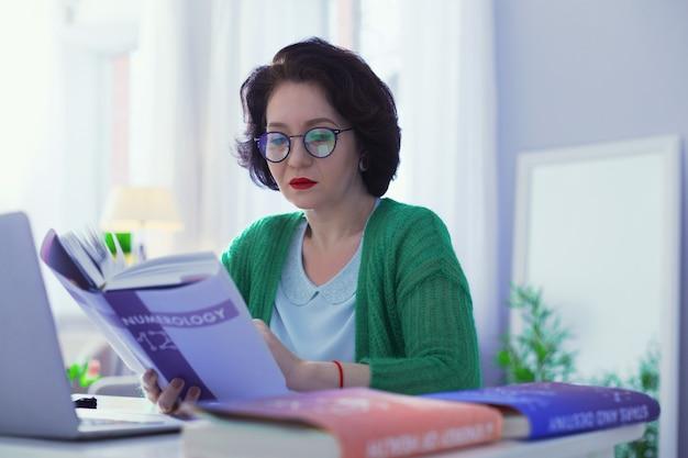 Während des lesens. intelligente gut aussehende frau, die eine brille trägt, während sie ein buch über numerologie liest
