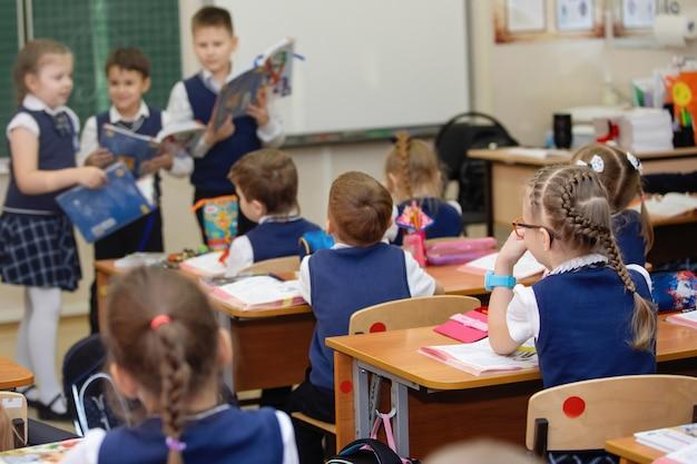 Während des unterrichts sitzen die schüler an ihren schreibtischen im klassenzimmer. grundschulbildung. selektiver fokus.
