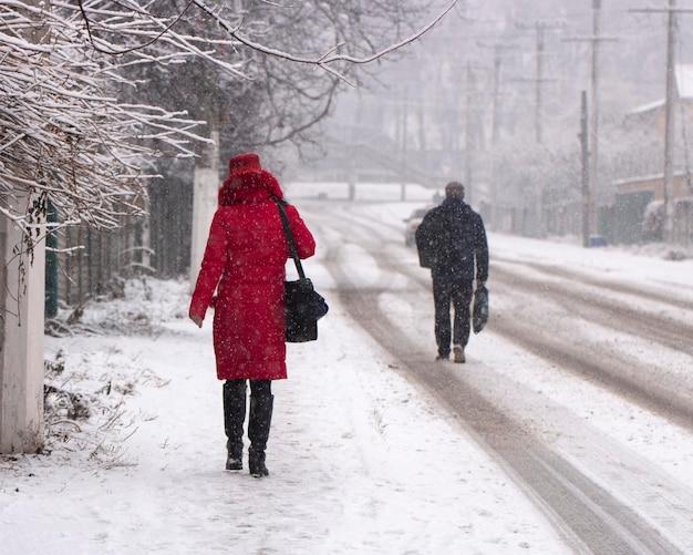 Während eines schneefalls gehen die menschen am frühen morgen eine verschneite straße entlang. stadtbild