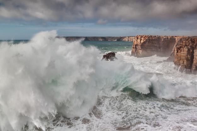 Während eines sturms brechen riesige wellen gegen die felsen.