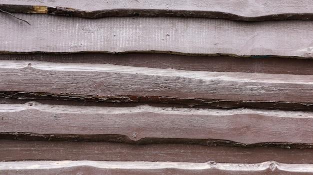 Wände aus alten, braun gestrichenen brettern, verkleidungen überlappten sich als hintergrund. abstrakter hölzerner hintergrund. die textur des zauns aus unbesäumten horizontalen brettern. kopieren sie platz, nahaufnahme.