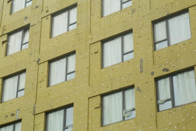 Wärmedämmung beim bau eines mehrfamilienhauses. installation eines industriellen hitzeschutzes auf einer hausbaustelle.