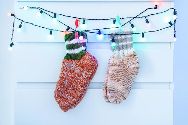 Wärmen sie die gestrickten wintersocken, die zu hause an den lichtern einer beleuchtungweihnachts hängen.