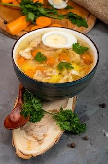 Wärmende suppe mit hühnchen, karotten, kartoffeln, kräutern und einem halben hartgekochten ei auf einem holzständer, vertikales foto.