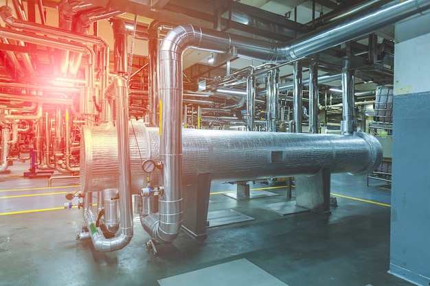 Wärmetauscher an der isolierung im prozessbereich der pipeline, die in der fabrik glänzende rostfreie chemikalien fließt.