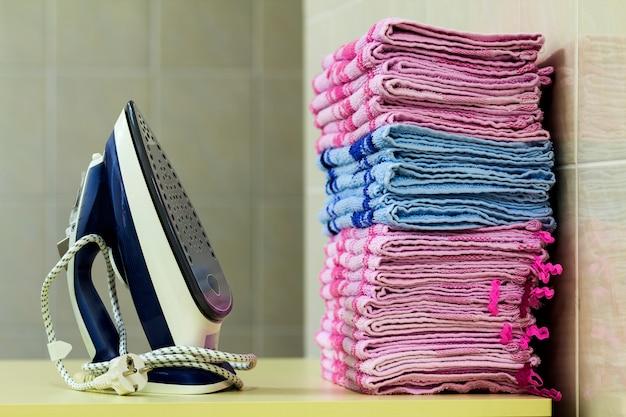 Wäsche mit dampferzeuger bügeln. ein stapel gebügelte tücher, die nahe bei dem eisen liegen. teflon-sohle mit kleinen löchern bedeckt.