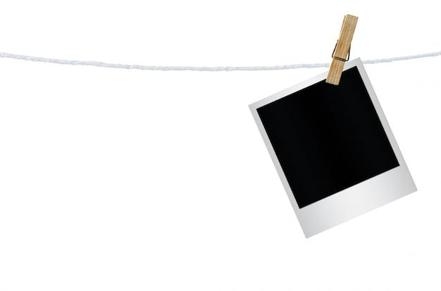 Wäscheklammer, die mit den leeren getrennten fotopapieren hängt.