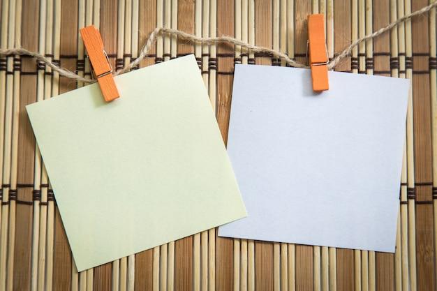 Wäscheklammer, die mit leerem briefpapier auf hölzerner hintergrundbeschaffenheit hängt.