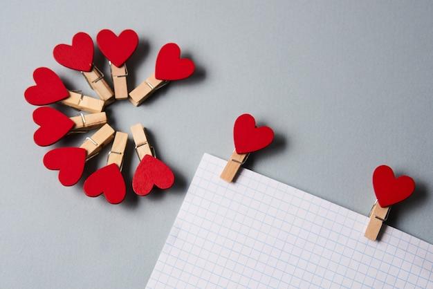 Wäscheklammern in form von herzen auf einem weißen blatt papier beschnitten ansicht valentinstagdekoration.