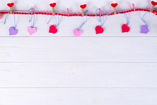 Wäscheklammern mit roten herzen auf einem band auf einem weißen hölzernen hintergrund. valentinstag