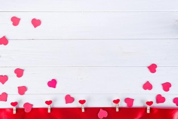 Wäscheklammern mit roten herzen auf einem roten band auf einem weißen hölzernen hintergrund von valentine day