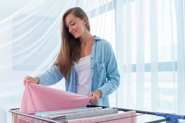 Wäscherei frau hängt sauberes nasses tuch auf wäschetrockner nach dem waschen zu hause. hausarbeit und haushalt