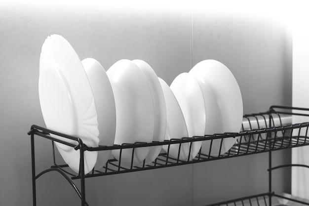 Wäscheständer mit sauberem weißem geschirr auf dem tisch im modernen kücheninnenhintergrundfoto