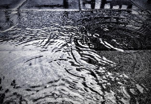Wässern sie auf straße am regnerischen tagesregen-saisonhintergrund