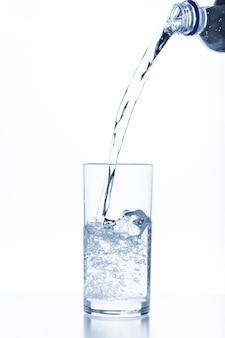 Wässern sie das gießen in das glas, das auf weißem hintergrund lokalisiert wird