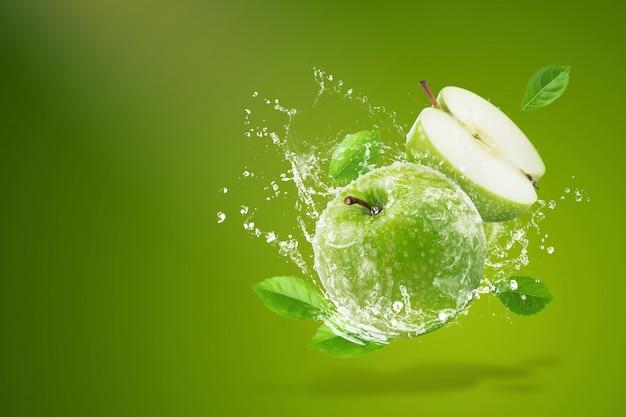 Wässern sie das spritzen auf frischem grünem apfel auf grünem hintergrund