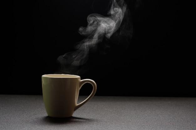 Wässern sie heiß auf holztisch, trinken sie dampf und kopieren sie raum, selektiven fokus. getränkewarmes konzept