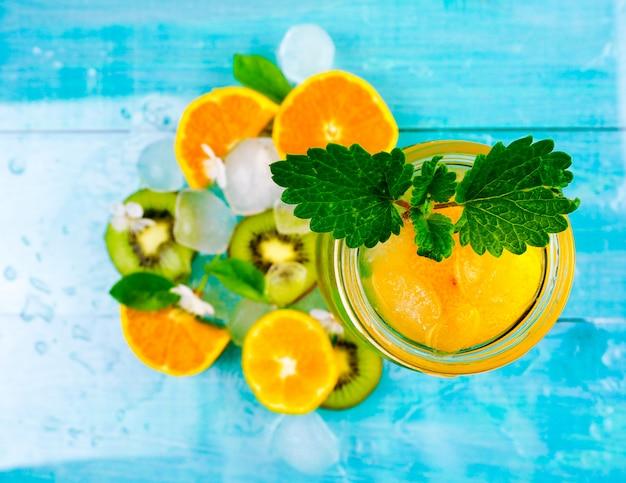 Wässern sie mit mandarine, minze und kleinen blumen auf hölzernem hintergrund. tiefenschärfe