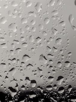 Wässern sie tropfen auf dem glas des fensterhintergrundes und regnen auf dem glas weg von der fensterstadt für hintergrund.