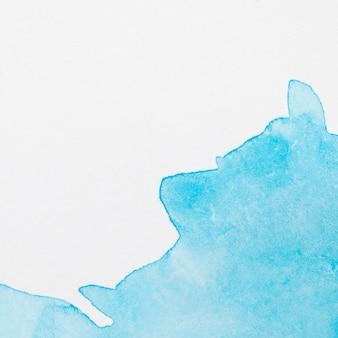 Wässriger blauer handgemalter fleck auf weißer oberfläche