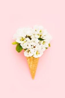 Waffel-eiscreme-kegel mit blühender birnenblume auf rosa hintergrundfrühlingskonzept-kopienraum für