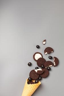 Waffel-eistüte mit schokoladenkeksen gefüllt mit schokoladen-dragees auf grauem hintergrund