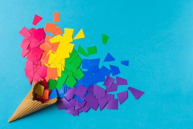 Waffelkegel in der nähe von papierstapeln in lgbt-farben