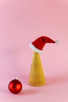 Waffelkegel in form eines weihnachtsbaumes mit einer weihnachtsmütze und einer weihnachtskugel auf einer rosa oberfläche.