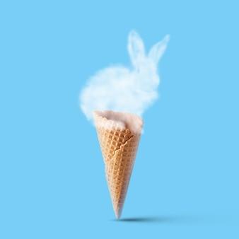 Waffelkegel mit einem kaninchen aus einer wolke auf blauem hintergrund isoliert. osterkonzept