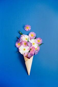 Waffelkegel mit kamillenblumenstrauß auf blauem hintergrund. flache lage, ansicht von oben