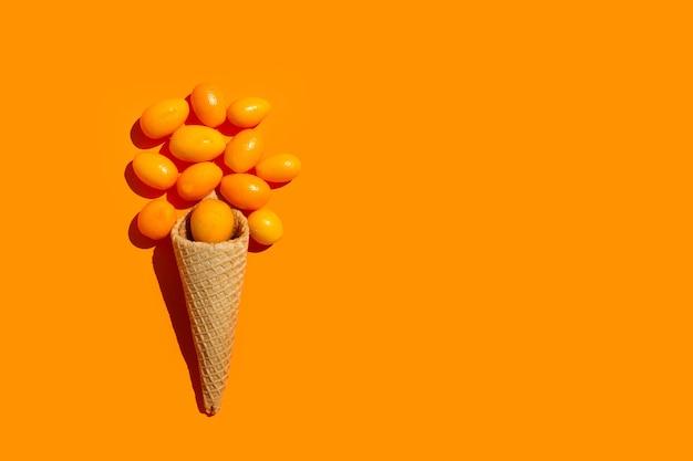 Waffelkegel mit kumquats auf orangefarbenem hintergrund mit kopierraum